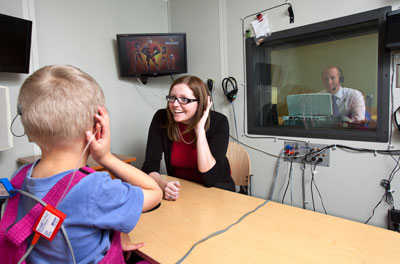 a boy and two teachers using hearing equipment in a sound booth