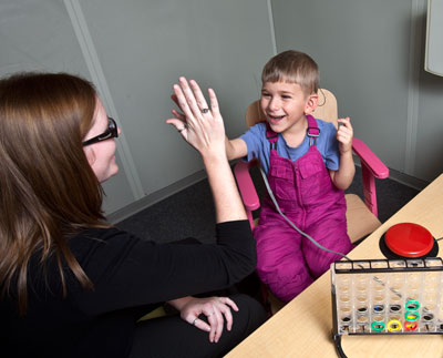 a boy playing a hearing test game, the teacher giving a congratulatory 'five'