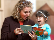 a sound beginnings teacher reading a book to a toddler
